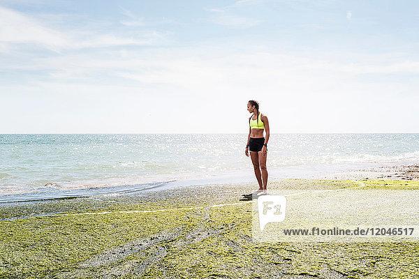 Junge Frau steht am Meer und schaut auf die Aussicht