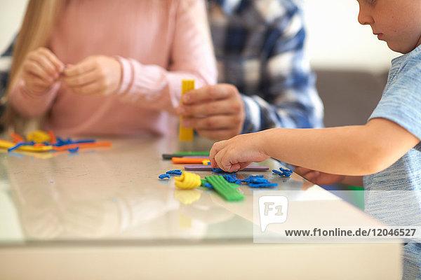 Vater  Sohn und Tochter  am Tisch sitzend  mit Modelliermasse spielend  Mittelteil