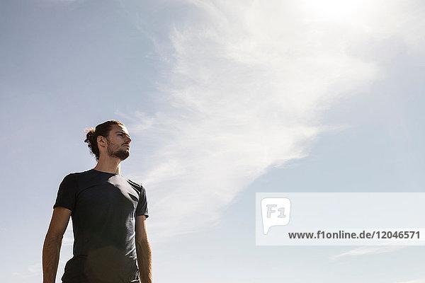 Junger männlicher Läufer blickt gegen blauen Himmel