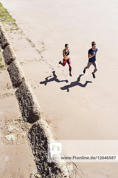 Young man and woman running along beach  elevated view