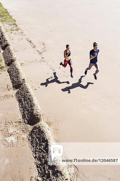 Junger Mann und Frau laufen am Strand entlang  erhöhte Ansicht