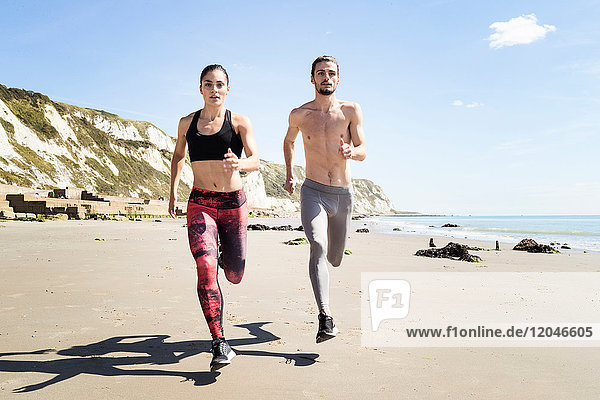 Young man and woman running along beach  front view