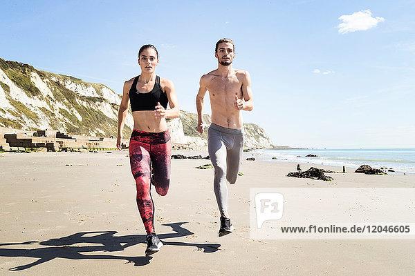 Junger Mann und Frau laufen am Strand entlang  Frontansicht