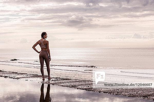 Junge Läuferin am Wasser mit Blick aufs Meer