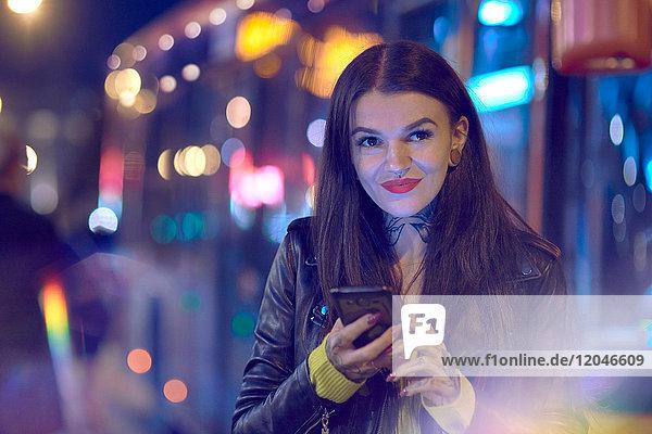Junge Frau nachts im Freien  Smartphone in der Hand haltend  Tätowierungen an Hand und Hals
