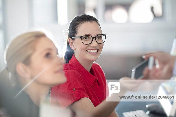 Junge Büroangestellte teilt ihr Smartphone mit einer Kollegin