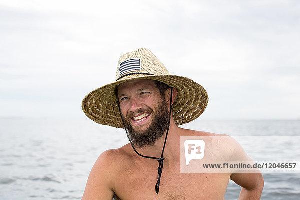 Mann im Wasser  Strohhut tragend  lachend