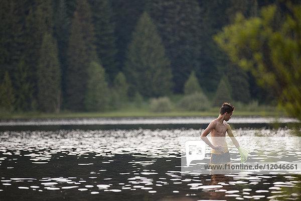 Teenage boy  fishing in lake  using net