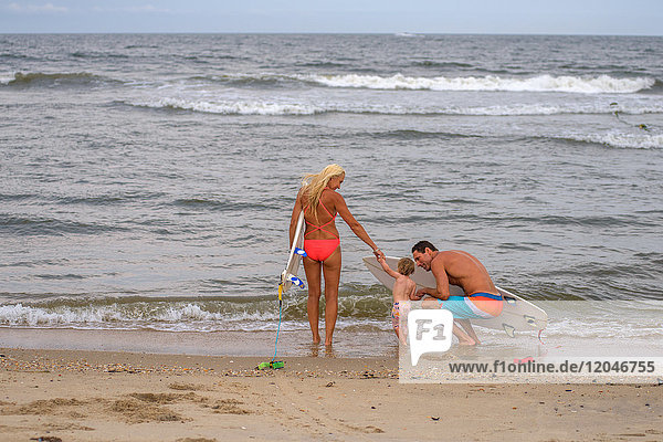 Rear view of surfing couple at water's edge with toddler daughter  Asbury Park  New Jersey  USA