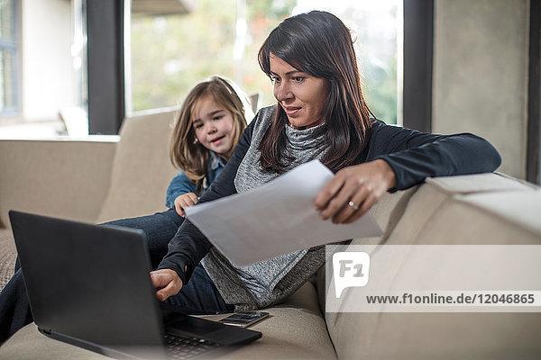 Mädchen sieht zu  während die Mutter am Laptop auf dem Sofa arbeitet