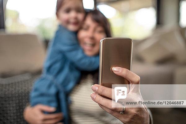 Leichte Konzentration einer reifen Frau,  die mit ihrer Tochter im Wohnzimmer ein Smartphone-Selfie mitnimmt