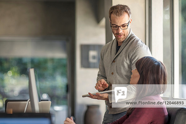 Geschäftsfrau und Mann treffen sich am heimischen Schreibtisch