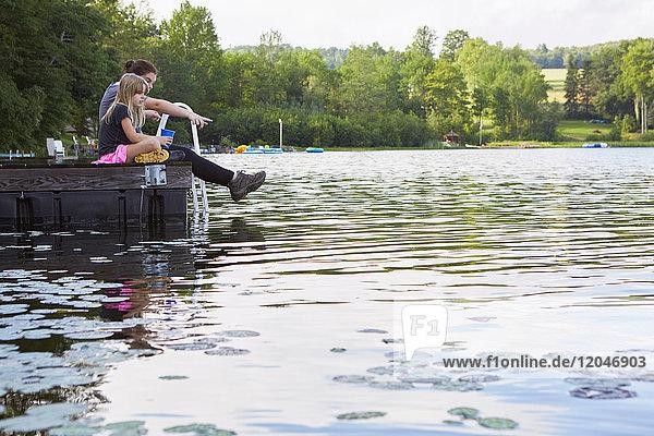 Zwei Mädchen sitzen auf einem Steg und schauen in den See