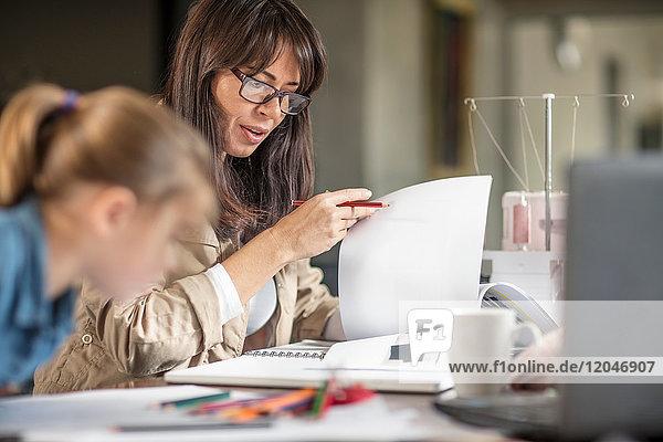 Reife Frau erledigt Papierkram  während die Tochter am Tisch zeichnet