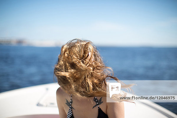 Woman on boat  hair blowing in wind  covering face
