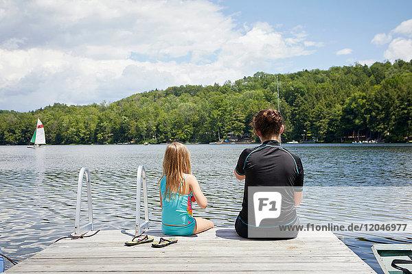 Zwei junge Mädchen sitzen auf einem Steg  Rückansicht