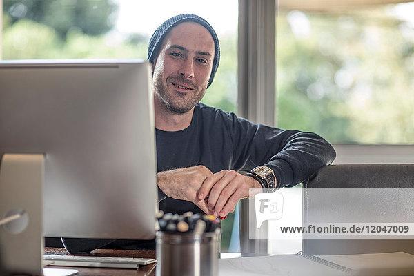 Porträt eines jungen männlichen Designers am heimischen Schreibtisch