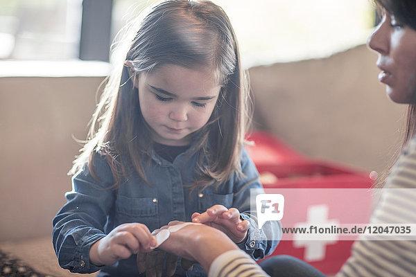 Mädchen klebt Pflaster auf die Hand der Mutter