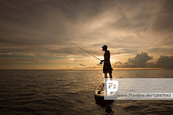 Man standing on paddle board  on water  at sunset  holding fishing rod