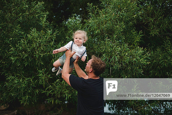 Mature man lifting up toddler son