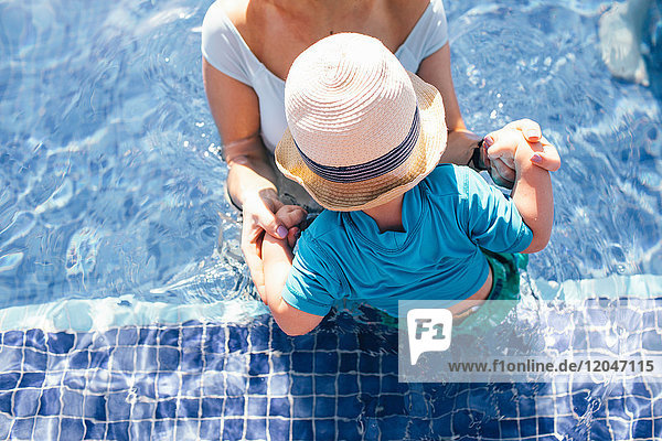 Mother and young son in outdoor swimming pool  elevated view  mid section
