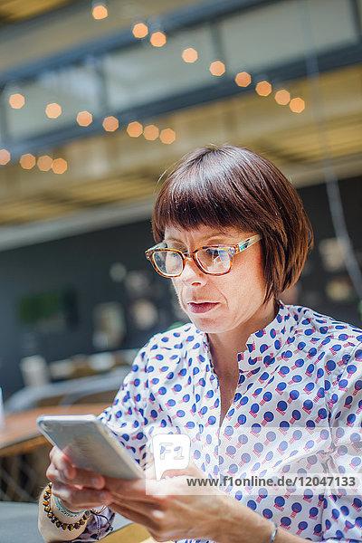 Frau im Büro mit Smartphone