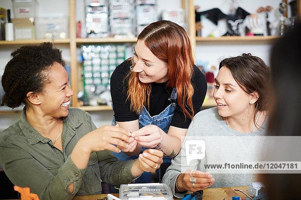 Cheerful multi-ethnic female engineers at workshop