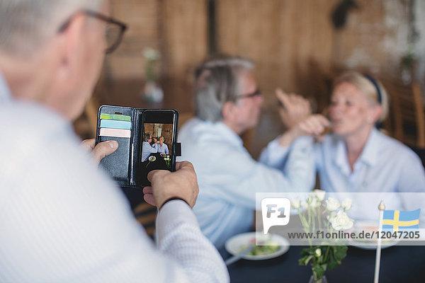 Senior man photographing couple having drinks in restaurant