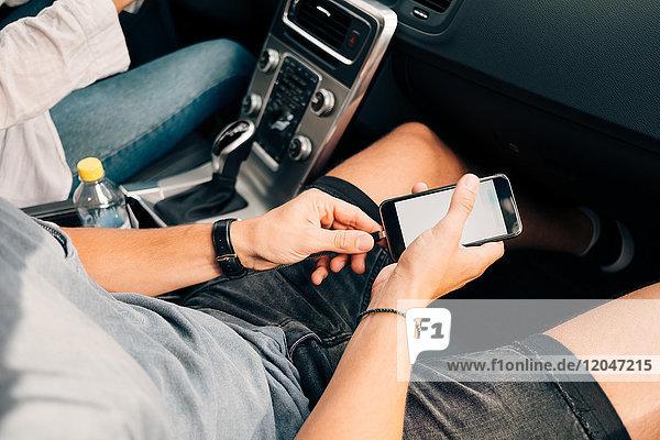 Hochwinkelansicht des Mannes  der das Smartphone im Auto auflädt.