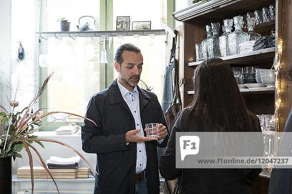 Reife Kunden stehen neben dem Glasregal im Geschäft