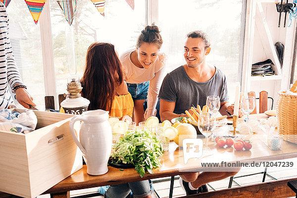 Fröhliche,  männliche und weibliche Freunde beim Zubereiten von Salat am Esstisch.