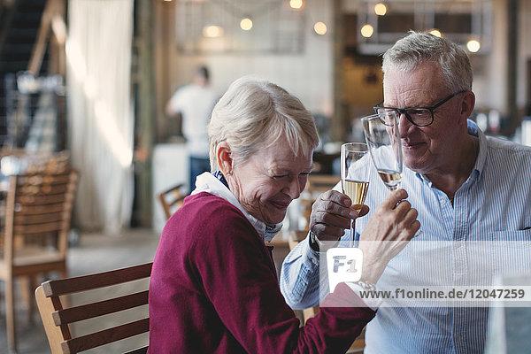 Liebende ältere Männer und Frauen genießen Champagner im Restaurant