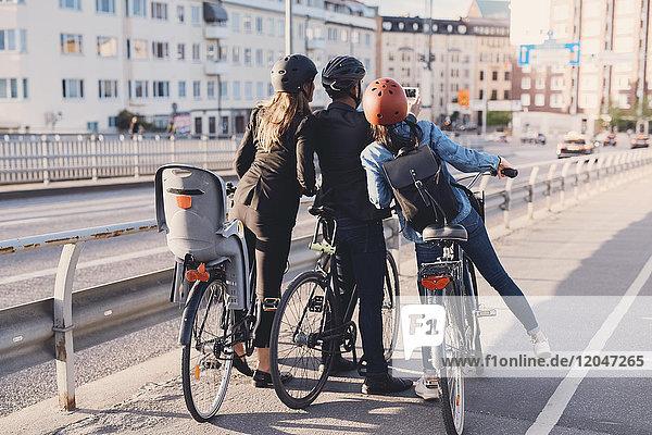 Rückansicht eines Mannes  der Selfie mit weiblichen Freunden mit Fahrrädern auf der Straße nimmt.