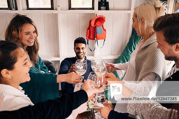 Hochwinkelansicht von glücklichen jungen Freunden  die während der Mittagsparty auf Weinglas anstoßen.