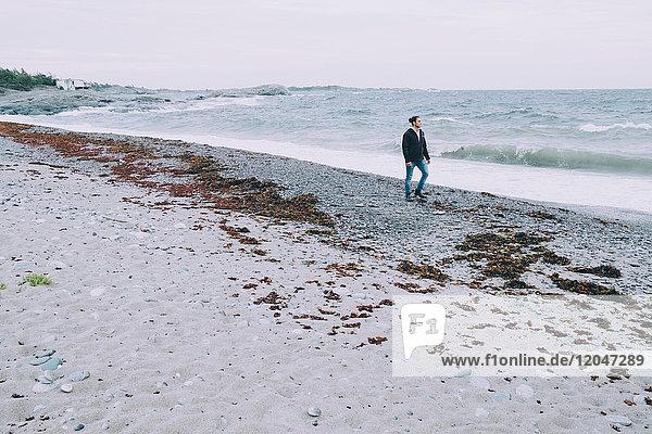 Volle Länge des jungen Mannes  der über das Meer am Strand läuft.