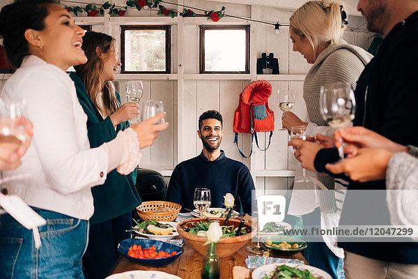 Fröhlicher junger Mann sieht Freunde an  die während der Mittagsparty Trinkgläser halten.
