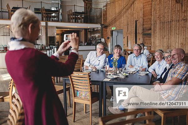 Seniorin fotografiert glückliche Freunde am Tisch im Restaurant