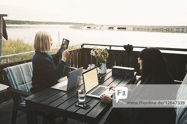 Frau mit digitalem Tablett im Sitzen mit Freunden  die den Laptop am Tisch in der Ferienvilla halten