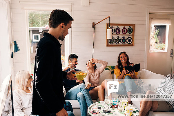 Young man holding bowl of snack while friends enjoying in cottage