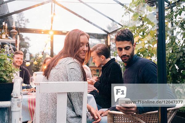 Low-Winkel-Ansicht von jungen Freunden mit smart während der Dinner-Party