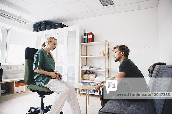 Krankenschwester im Gespräch mit Patientin im Büro