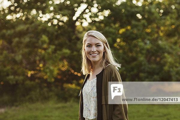 Porträt einer lächelnden jungen blonden Frau  die an Bäumen steht.