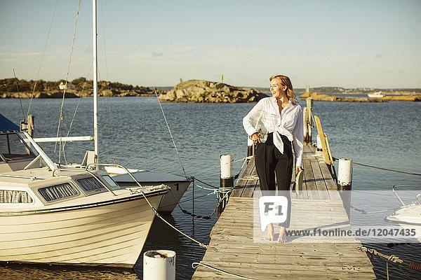Volle Länge der lächelnden jungen Frau  die auf dem Steg am Hafen gegen den Himmel steht.