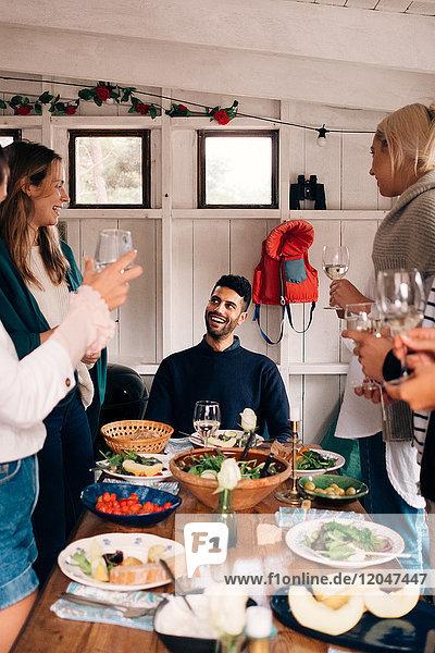 Glücklicher Mann sieht Freunde an  die während der Mittagsparty Trinkgläser halten.