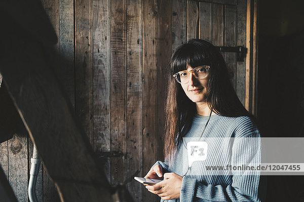 Porträt einer lächelnden Frau mit Smartphone an der Holzwand in der Ferienvilla