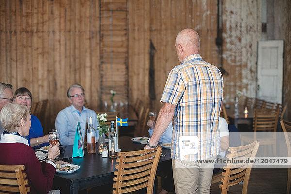 Seniorenrede vor Freunden beim Mittagessen im Restaurant