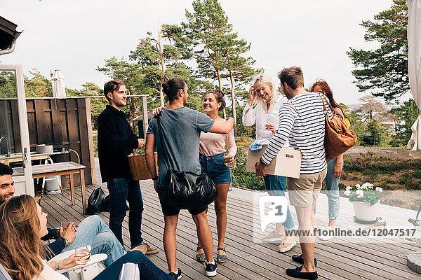 Fröhliche Freunde begrüßen sich auf dem Cottage-Deck