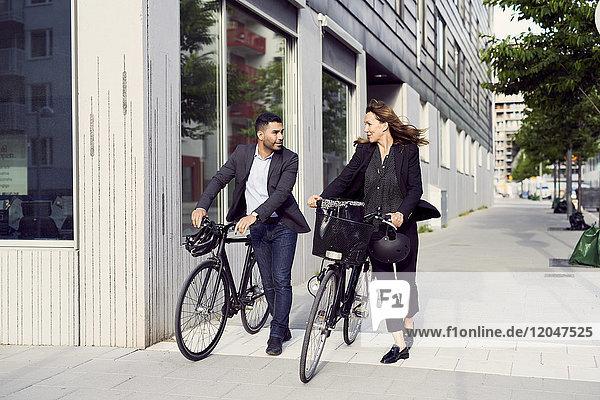 Volle Länge der Geschäftsleute  die mit Fahrrädern auf dem Bürgersteig in der Stadt laufen.