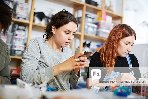 Young female technician using smart phone while sitting amidst colleagues at workshop