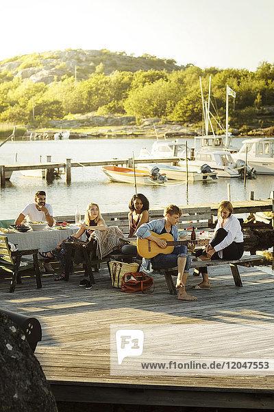 Freunde  die dem Mann beim Gitarrespielen während der Party im Hafen an einem sonnigen Tag zuhören.